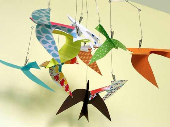Яркие птицы-оригами над кроваткой младенца